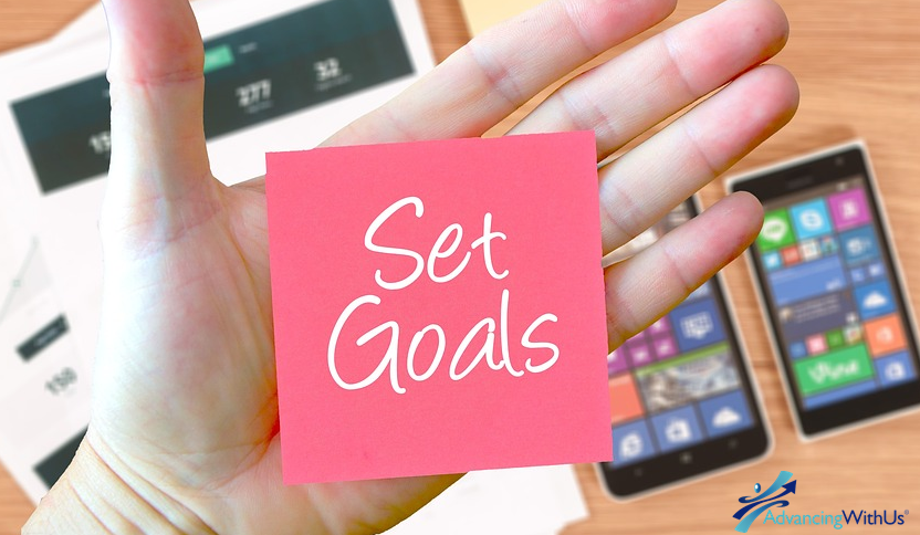 Business goals with AdvancingWithUs on a post-it note.