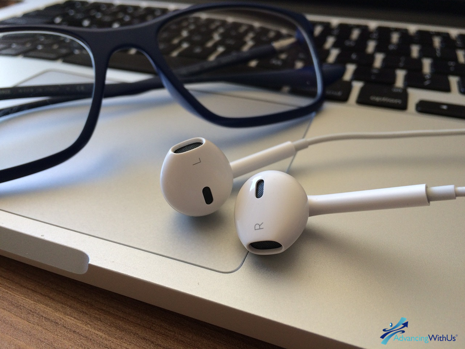 earbuds and glasses ready to listen to business podcast as computer